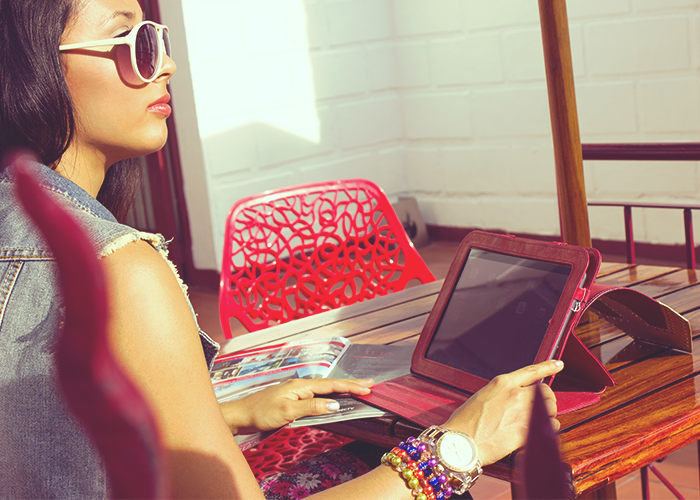 tfd_woman-sitting-on-red-table-with-ipad-working