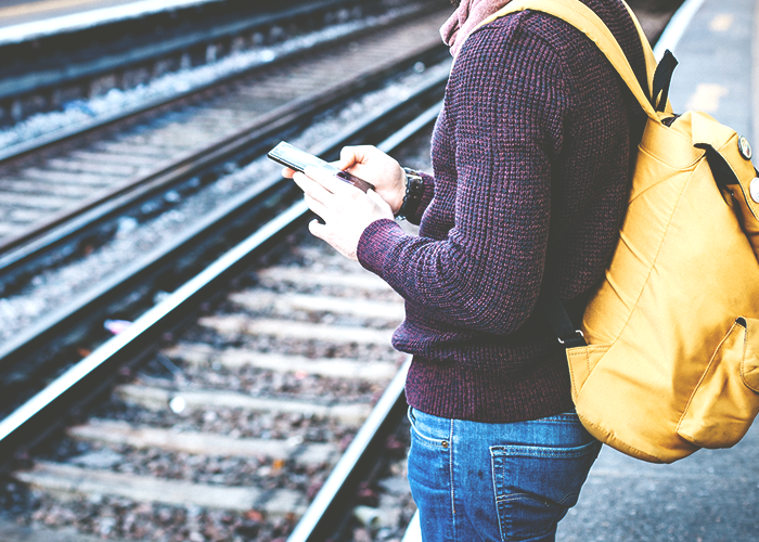 man-reading-on-phone-by-train-tracks