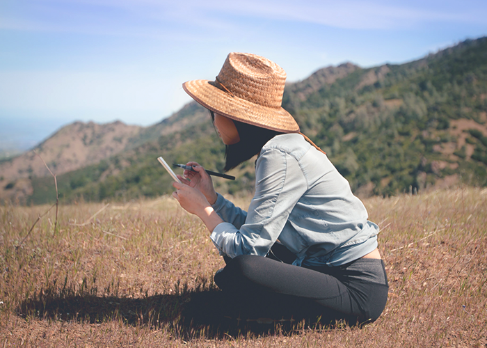 young-woman-sitting-on-grass-writing