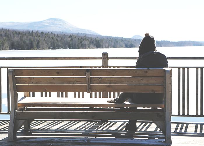 young-women-sitting-on-bench-near-lake