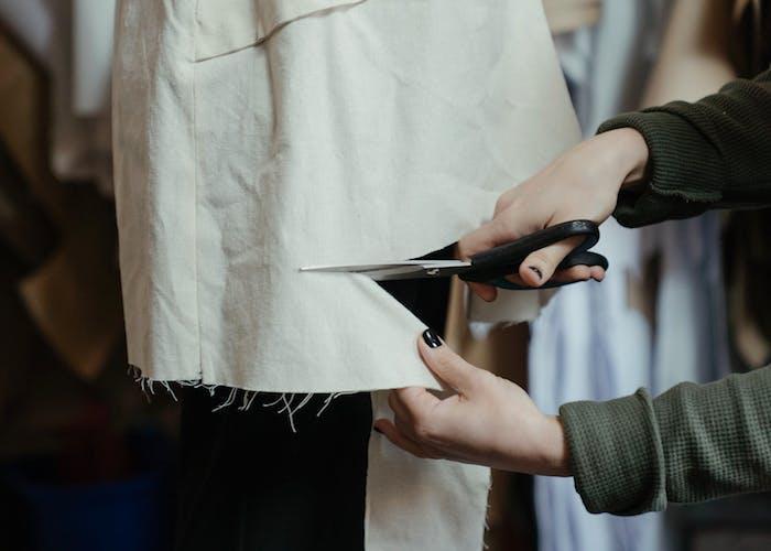 Woman cutting clothing with a pair of scissors for a DIY fashion style