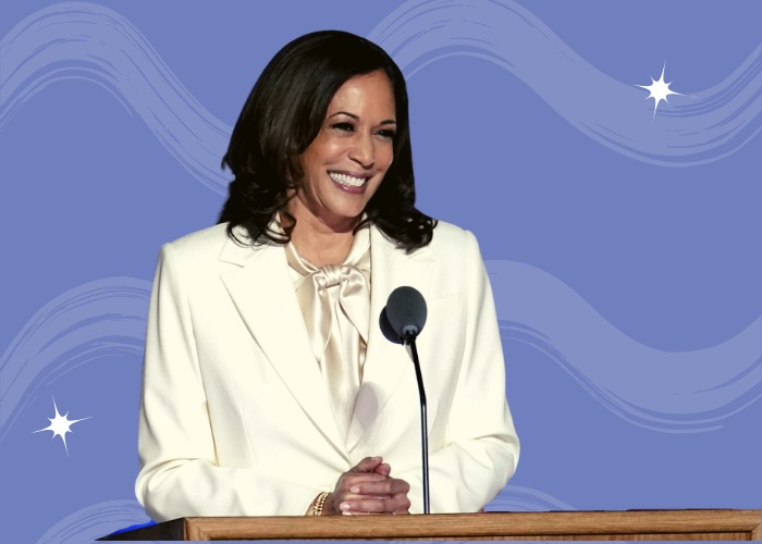 Kamala Harris, Vice President of the United States of America, standing at a podium in cream colored suit. Smiling in front of the microphone.